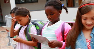 Le groupe de l'école badine utilisant le comprimé numérique et le téléphone portable banque de vidéos