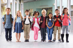 Le groupe de l'école primaire badine la position dans le couloir d'école photographie stock libre de droits