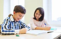 Le groupe de l'école badine l'essai d'écriture dans la salle de classe Photo libre de droits