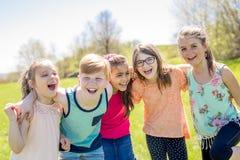 Le groupe de l'enfant ont l'amusement sur un champ Photos stock