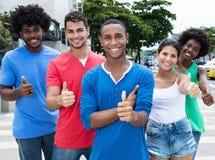 Le groupe de l'homme heureux de Caucasien et d'afro-américain et la femme montrent Photos stock