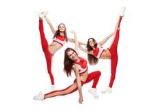 Le groupe de la jeune équipe féminine de majorettes se tiennent dans la pose avec le ` s de pom-pom sur le fond d'isolement image stock