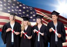 Le groupe de personnes dans l'obtention du diplôme habillent la position contre le drapeau américain Images stock