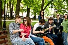 Le groupe de personnes en stationnement de ville écoutent musique. Photos libres de droits