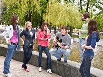 Le groupe de personnes en stationnement de ville écoutent musique. Image libre de droits