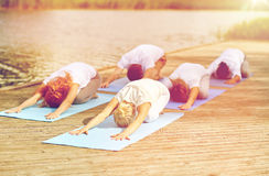 Le groupe de personnes faisant le yoga s'exerce dehors Image stock