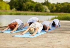 Le groupe de personnes faisant le yoga s'exerce dehors Photo libre de droits