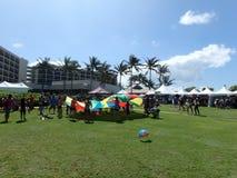Le groupe de personnes jettent des boules en air avec l'aide du cercle d'arc-en-ciel Images stock