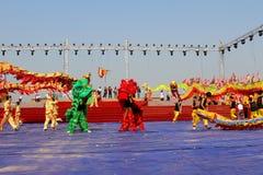 Le groupe de personnes le lion de représentation et le dragon dansent Images libres de droits