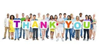 Le groupe de personnes multi-ethniques tenant les plaquettes qui forment remercient Yo Photo stock