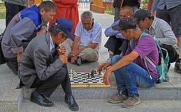 Le groupe de personnes observe le jeu d'échecs sur Images stock