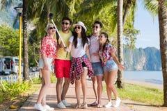 Le groupe de personnes prennent Selfie avec l'appareil-photo d'action sur le bâton tout en marchant en parc de palmier sur la pla Photographie stock libre de droits