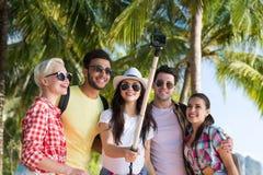 Le groupe de personnes prennent Selfie avec l'appareil-photo d'action sur le bâton tout en marchant en parc de palmier sur la pla Photos libres de droits