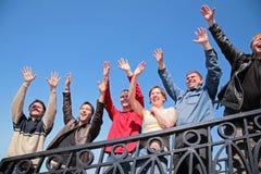 Le groupe de personnes que le stand avec des mains s'est soulevés saluent dedans Photos stock