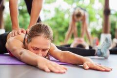 Le groupe de personnes s'étirant avec l'instructeur de forme physique sur des pilates classe photos stock