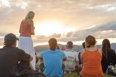 Le groupe de personnes s'asseyant sur l'herbe et apprécient le coucher du soleil Photographie stock