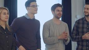 Le groupe de personnes se tenant devant des affaires donnent des leçons particulières, écoutant et discutant une présentation photo stock
