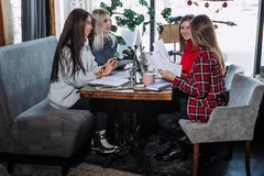 Le groupe de personnes travaillant aux affaires projettent au café, se reposant à la table avec des feuilles de papier et d'ordin Photos libres de droits