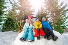 Le groupe de petits enfants s'asseyent sur le mur de neige en parc Photos stock