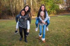 Le groupe de quatre enfants jouant et donnant sur le dos monte Image libre de droits