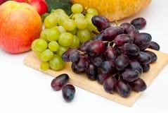 Le groupe de raisins verts et noirs porte des fruits au-dessus du blanc sur le fond de conseil en bois Image libre de droits