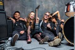Le groupe de rock s'asseyant sur le plancher tout en se reposant après préparent Image libre de droits