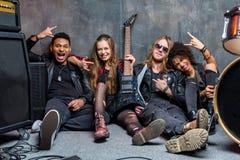 Le groupe de rock s'asseyant sur le plancher tout en se reposant après préparent Photo libre de droits