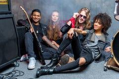 Le groupe de rock s'asseyant sur le plancher tout en se reposant après préparent dans le studio Images libres de droits
