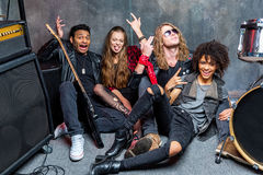 Le groupe de rock s'asseyant sur le plancher tout en se reposant après préparent dans le studio Photo stock