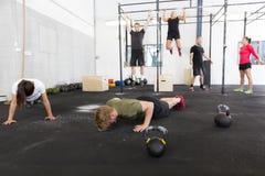Le groupe de séance d'entraînement fait des exercices au gymnase de forme physique Images libres de droits