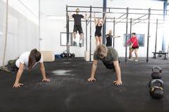 Le groupe de séance d'entraînement forme des exercices au gymnase de forme physique Photos libres de droits