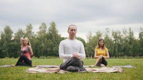 Le groupe de sportifs exécute la formation dehors dans un parc vert - la fille blonde dort pendant la méditation banque de vidéos