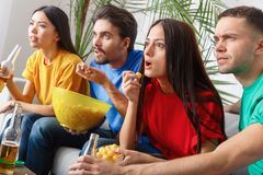 Le groupe de supporters d'amis regardant la rencontre dans des chemises colorées excitées a concentré le plan rapproché Photos libres de droits