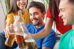 Le groupe de supporters d'amis regardant la rencontre dans des chemises colorées grillent le plan rapproché Image stock