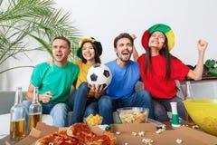Le groupe de supporters d'amis regardant la rencontre dans des chemises colorées team la victoire Images stock