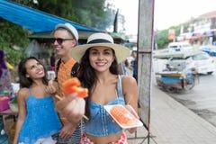 Le groupe de touristes mangent la marche fraîche de fruits tropicaux des jeunes gais de ville asiatique des vacances ensemble Photos stock