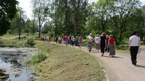 Le groupe de touristes marchent dans le jardin botanique près de l'étang en été banque de vidéos