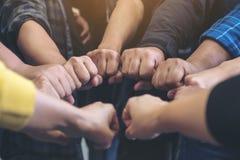 Le groupe de travail d'équipe d'affaires joignent leurs mains ainsi que la puissance et réussis