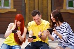 Le groupe de trois amis jouent le jeu vidéo mobile dehors, la fille et photo libre de droits