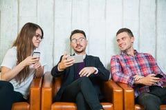Le groupe de trois smartphones de prise des jeunes parlent et sourient Photo stock