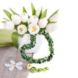 Le groupe de tulipes blanches et de décorations assorties de ressort sur le bois est Images stock