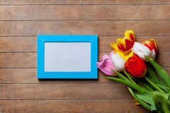 Le groupe de tulipes et la photo bleue encadrent le mensonge sur la table Images stock