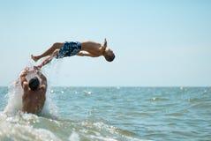 Le groupe de types se tenant en mer a jeté en l'air vers le haut de l'homme Photo libre de droits