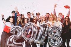 Le groupe des beaux jeunes dans des chapeaux de Santa tenant l'argent a coloré des ballons de nombre et des confettis colorés Image libre de droits