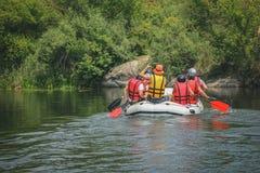 Le groupe des hommes et de femmes, apprécient l'eau transportant l'activité par radeau à la rivière image stock
