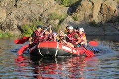 Le groupe des hommes et de femmes, ont plaisir à transporter l'activité par radeau à la rivière photos libres de droits