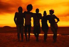 Le groupe des hommes et les femmes arment dans le bras à la plage sur le coucher du soleil Photographie stock