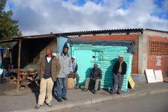 le groupe des hommes marchent sur la rue dans la banlieue noire de Khayelitsha images stock