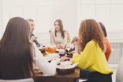 Le groupe des jeunes à la table de dîner, amies font la fête Photos stock