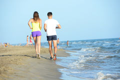 Le groupe des jeunes courant dans le sable sur le rivage d'une plage par la mer au coucher du soleil pendant des vacances d'été e Photos stock